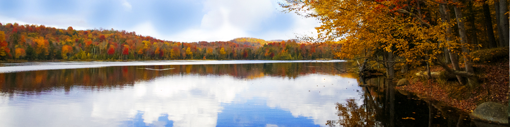 Pictured is one of the lakes in Old Forge during the fall. The red and orange colors from the trees are being reflected in the water. One of the many beautiful fall scenes during the fall season.