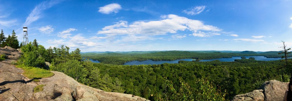 Vantage point from Bald Mountain. Scenic views include a tower to the left, the green pine trees, and part of the lake. One of the many things to experience in the Adirondacks.