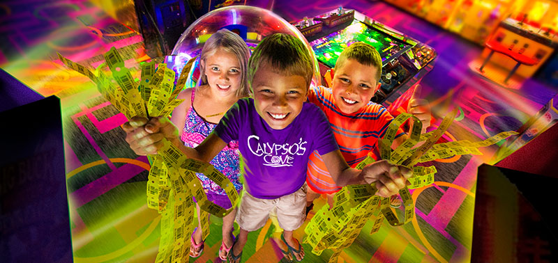 Three children in the arcade smiling, and holding up their tickets.