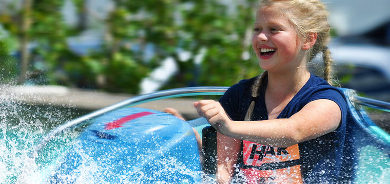 Young girl enjoying a ride on the bumper boats at Calypso's Cove.