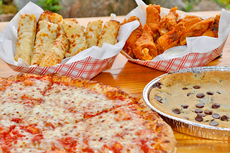 Some of the food options that are available at Calypso's Cove. Shown is pizza and wings. a big chocolate chip cookie cake, and bread sticks.