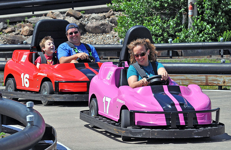 Three guests enjoying a ride on the go-karts at Calypso's Cove.