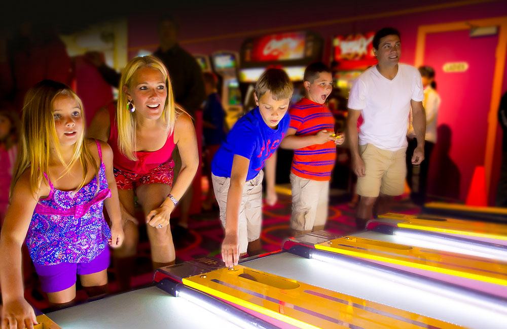 Adults and children enjoying a game of skeet-ball in the arcade at Calypso's.