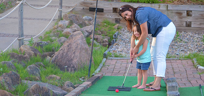 Two guests getting ready to play a game of mini-golf at Calypso's Cove.