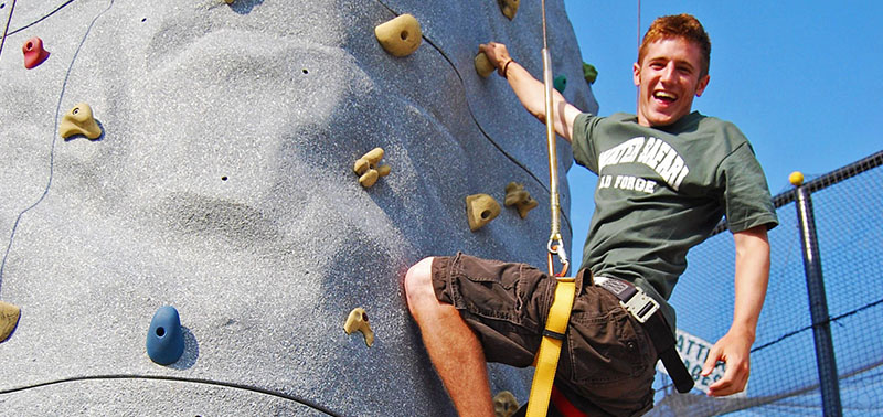A guest smiling while getting ready to take a climb on the rock climbing wall.