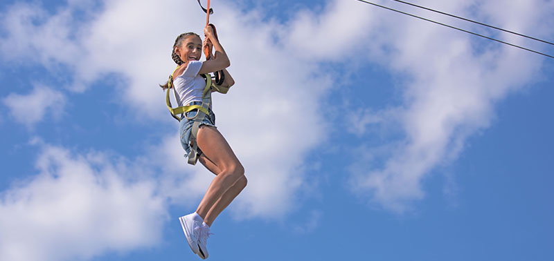 A guest smiling while taking a ride on the zip-line at Calypso's Cove.