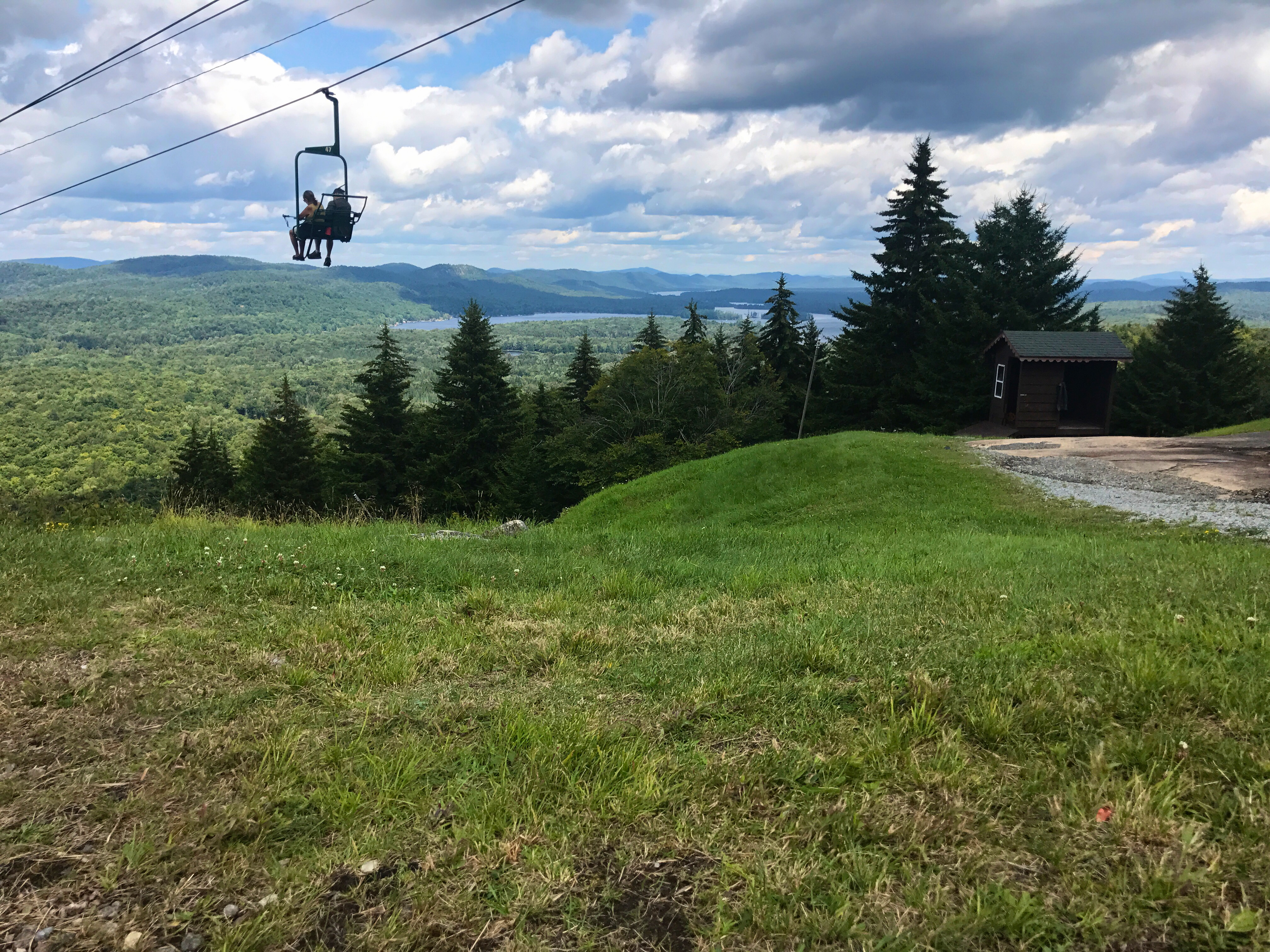 View from McCauley Mountain. The picture portrays two people enjoying a ride on the chair lift located at McCauley Mountain, and a view of the mountains, trees, and lakes.